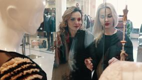 Two women choose clothes in the store near the storefront. Two young women choose clothes in a store near the shop window stock footage