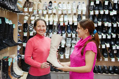 Two women chooses high boots Stock Photo