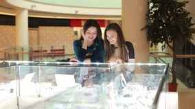 Two women chooses jewelry at shop. Two young girls in a big shopping center look in the showcase. Shopping time stock video