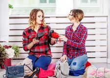 Two women choosing shoes of her wardrobe. The concept of fashion. Style, friendship stock photography