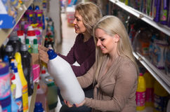 Two women choosing some detergents. In the shop Royalty Free Stock Photos