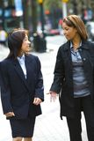 Two women on city sidewalk. A view of two multi-racial women, talking together as they walk along a city sidewalk Stock Photos