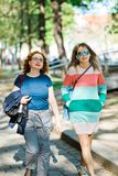 Two women in the city walking together - woman with color gaps on dress stock images