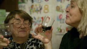 Two women clanging glasses. Old and middle-aged women toasting and drinking red wine at home stock video footage