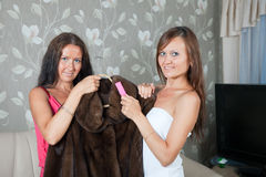 Two women cleaning fur coat Royalty Free Stock Photos