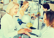 Two women clients having manicure done in nail salon stock image