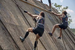 Two women climbing with ropes on a wall stock images