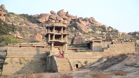 Two women climbing up the stairs and entering in the ruins of temple. HAMPI, INDIA - 28 JANUARY 2015: Two women climbing up the stairs and entering in the ruins stock video