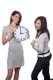 Two women with clock. Two women with a clock showing three royalty free stock image