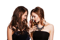 Two women in cocktail dresses. isolated on white. Young beautiful women in elegant black cocktail dresses celebrating Stock Photo