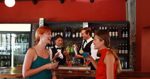 Two women with cocktail drinks talking to each other at counter. In bar 4K stock footage