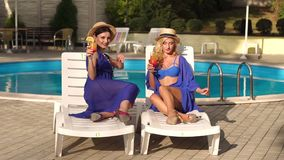 Two women with cocktails resting on sun loungers. Two beautiful sexy girls in bikini and silk dresses sitting on the sun loungers by the pool with a cocktail stock footage