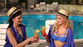 Two women with cocktails resting on sun loungers. Two beautiful sexy girls in bikini and silk dresses sitting on the sun loungers by the pool and clink glasses stock footage