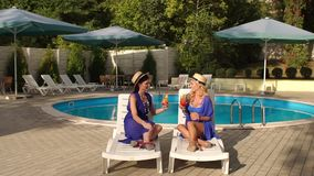 Two women with cocktails on sun loungers by pool. Two luxurious girls relax with cocktails on the sun loungers near the pool in the summer stock video