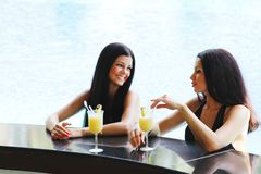 Two women with cocktails in swimming pool Royalty Free Stock Images