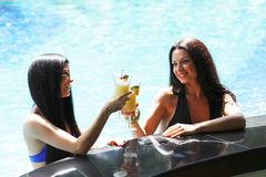 Two women with cocktails in swimming pool Stock Photography