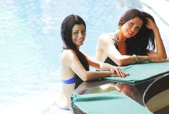 Two women with cocktails in swimming pool Stock Images