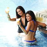 Two women with cocktails in swimming pool Stock Image