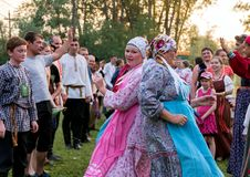 Two women in colorful Russian costumes, dancing for the time of the annual Intl festival. SHUSHENSKOE, RF - July 12, 2014: Two women in colorful Russian royalty free stock image