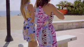 Two women in colorful summer dresses stock video footage