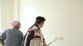 Two women colourer paint the wall. Using a paint roller stock footage