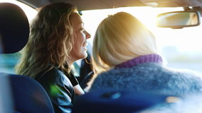 Two women communicate inside the car. Laugh, smile, enjoy the tablet. Rear view. Two women communicate inside the car. Laugh, smile, enjoy the tablet stock footage