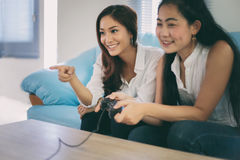 Two women Competitive friends playing video games and excited ha. Ppy cheerful at home Royalty Free Stock Photo