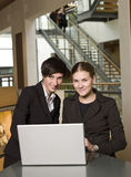 Two women and a computer. Two women in front of a laptop Stock Images