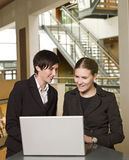 Two women and a computer. Two businesswomen in front of a laptop Royalty Free Stock Image