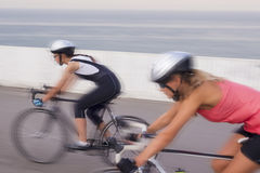 Two women compete on the race bikes. blurred  imag Royalty Free Stock Photography