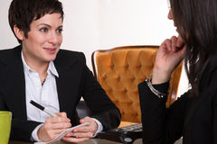 Two Women Conducting Job Interview Computer Desk Office. Two professional women consult about a job opening Stock Photo