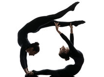 Two women contorsionist  exercising gymnastic yoga silhouette. Two women contorsionist practicing gymnastic yoga in silhouette   on white background Stock Photo