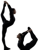 Two women contorsionist  exercising gymnastic yoga silhouette. Two women contorsionist practicing gymnastic yoga in silhouette   on white background Royalty Free Stock Photo