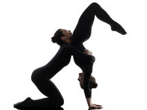Two women contorsionist  exercising gymnastic yoga silhouette Royalty Free Stock Images