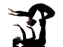Two women contortionist  exercising gymnastic yoga silhouette. Two women contortionist practicing gymnastic yoga in silhouette   on white background Stock Photo