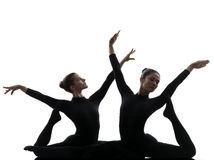 Two women contortionist  exercising gymnastic yoga silhouette Royalty Free Stock Image