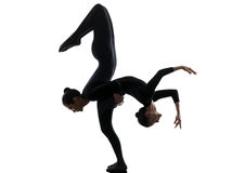 Two women contortionist  exercising gymnastic yoga silhouette. Two women contortionist practicing gymnastic yoga in silhouette   on white background Stock Photos