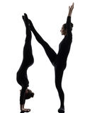 Two women contortionist  exercising gymnastic yoga silhouette Royalty Free Stock Photography