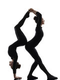 Two women contortionist  exercising gymnastic yoga silhouette Stock Image