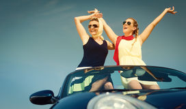Two women in convertible car enjoying car trip Stock Photography