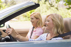 Two women in convertible car smiling Stock Images