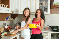 Two women cooking at kitchen stock image