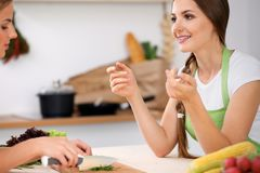 Two women is cooking in a kitchen. Friends having a pleasure talk while preparing and tasting salad. Friends Chef Cook Royalty Free Stock Photo