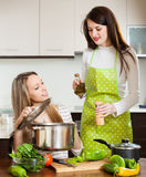 Two women cooking in pan Stock Photos