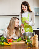 Two   women cooking something together Stock Photos