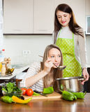 Two women cooking something with vegetables. At home kitchen. Focus on blonde royalty free stock photography