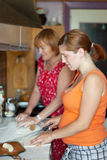 Two women cooks pie Stock Photography
