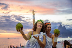Two women in the costumes of Greek Goddesses on the background of the beautiful sundown at Ipanema beach, Carnaval Royalty Free Stock Photo