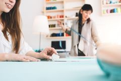 Two women create designer clothing in sewing studio. Dressmaker working with cloth in showroom. Small business royalty free stock image