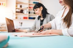 Two women create designer clothing in sewing studio. Dressmaker working with cloth in showroom. Small business stock photos